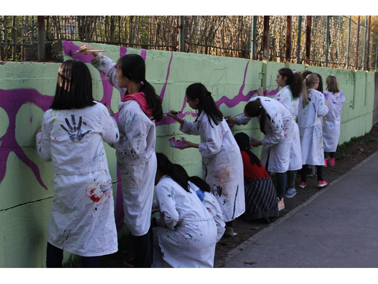 Girls painting school's fence at no energy day sleepover.