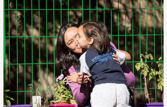A kindergarten girl and her mother hugging in the playground