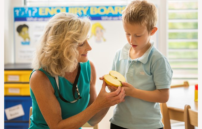 Student and teacher looking at a cut apple
