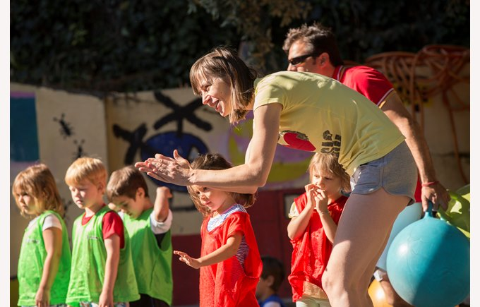 A kindergarten mother cheers on children taking part in sports day