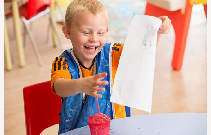 A kindergarten boy making a bubble painting in an art class
