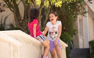 Two primary school girls laughing in the playground