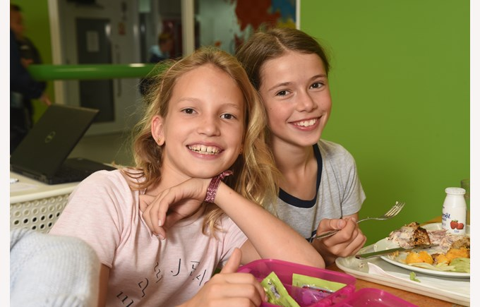 Two girls enjoying lunch in the ICS cafeteria