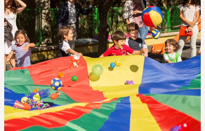 Kindergarten children play a game with a parachute and balls