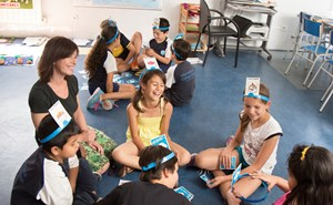 A group of primary school children sit down with their teach and play a game