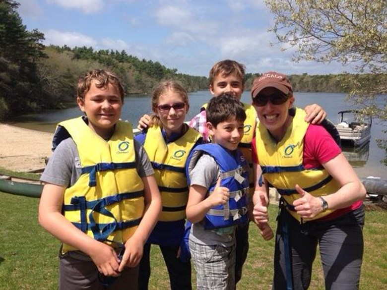 A teacher poses in life jackets with a group of students