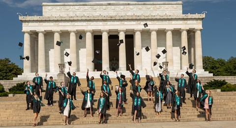 Graduates throw their hats outside of Lincoln Memorial