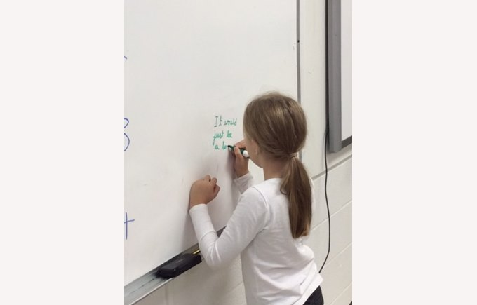 Young student writing on whiteboard