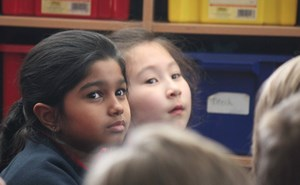 Two young girls listen to their teacher