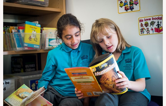 BISW Private British International School of Washington in DC Smart primary students reading together in library