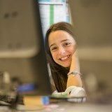 A girl smiles at the camera in the computer lab