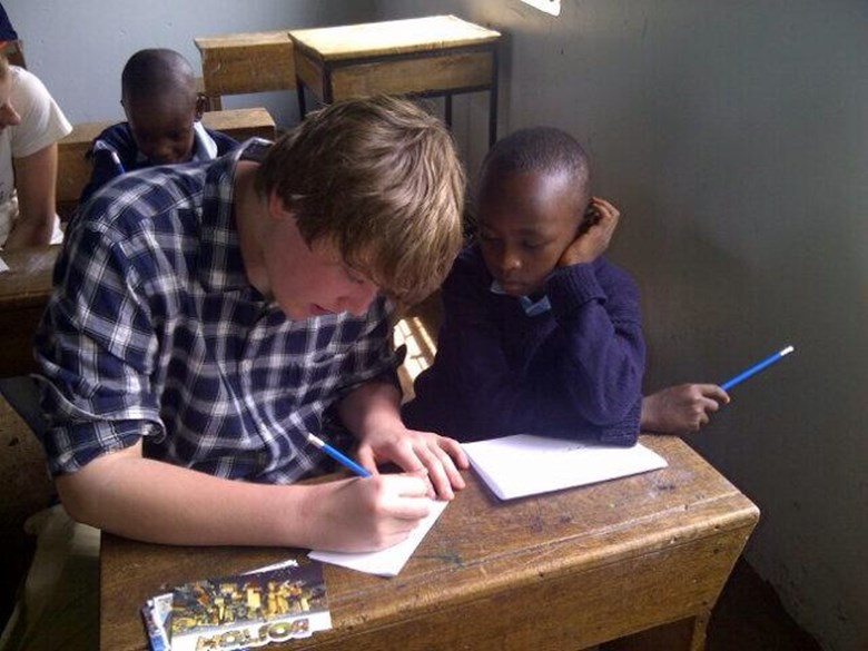 A student teaches a boy in Tanzania