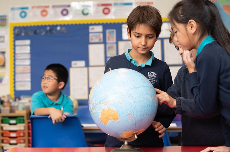 Lower School Students Looking at Globe