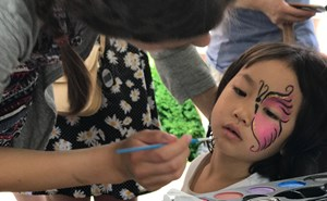 A Year 13 student paints a younger students face at an event.