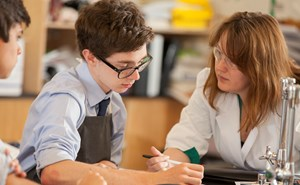 student having a discussion with a teacher in a science lab