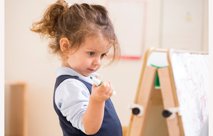 A young girl works at an easel