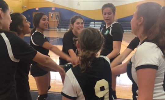 BISW girls varsity volleyball team huddles before another set begins.