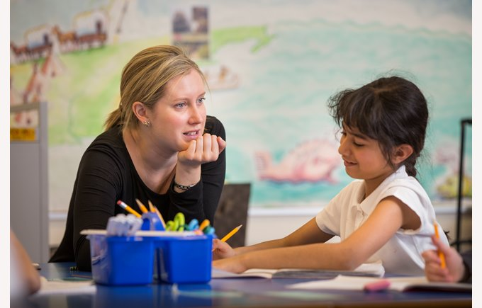 A teacher works with a young student