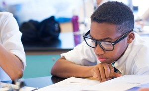 A secondary student intensely studies his lab workbook.