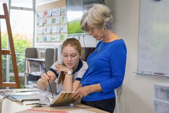 Student looking at book with teacher