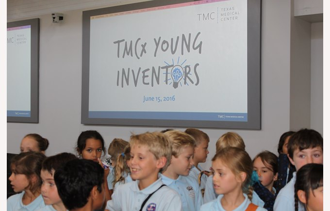 Students stand in front of presentation for TMCx Young Inventors