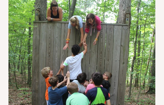 BISW Private British International School of Washington in DC students help each other to climb a wall for team building.