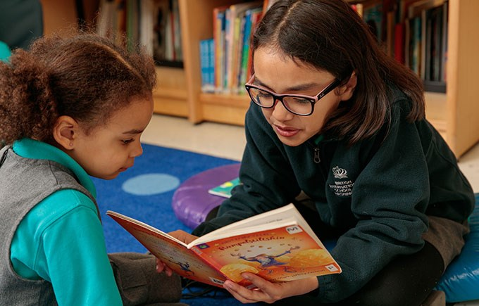 BISW Private British International School of Washington in DC Year 6 student reads with her PK4 Reading buddy.