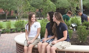 High school girls talking on the green space of The Village School's patio