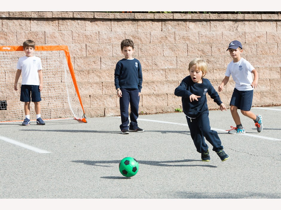 A young boy plays soccer at recess