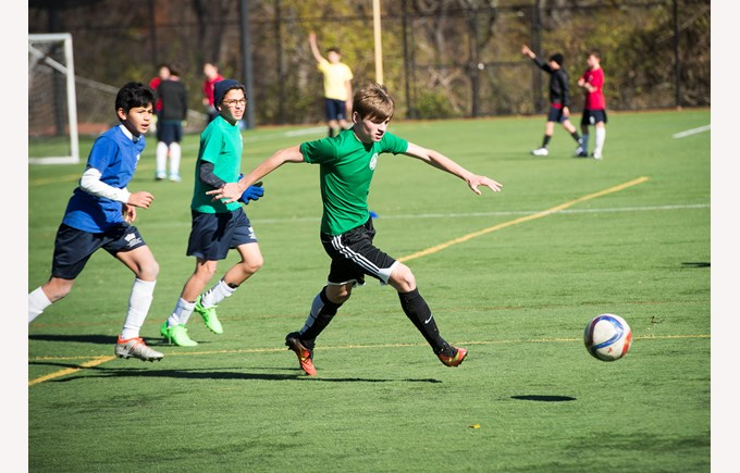 BISW Private British International School of Washington in DC Talented Student playing football soccer outside on field