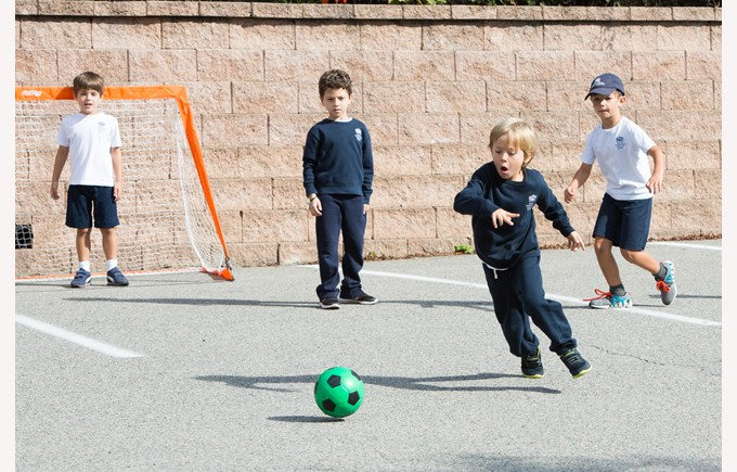 A group of boys play soccer